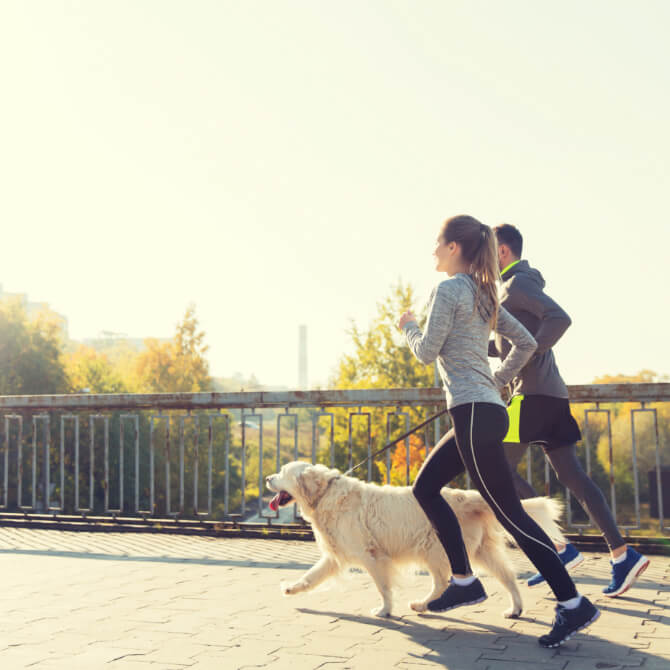 a man and a woman running outside with their dog