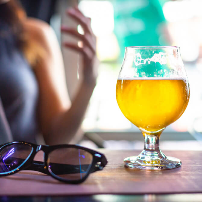 a glass of beer on a table next to black rimmed glasses