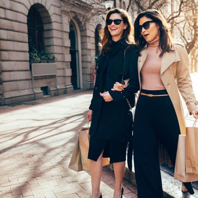 two women walking outside with shopping bags